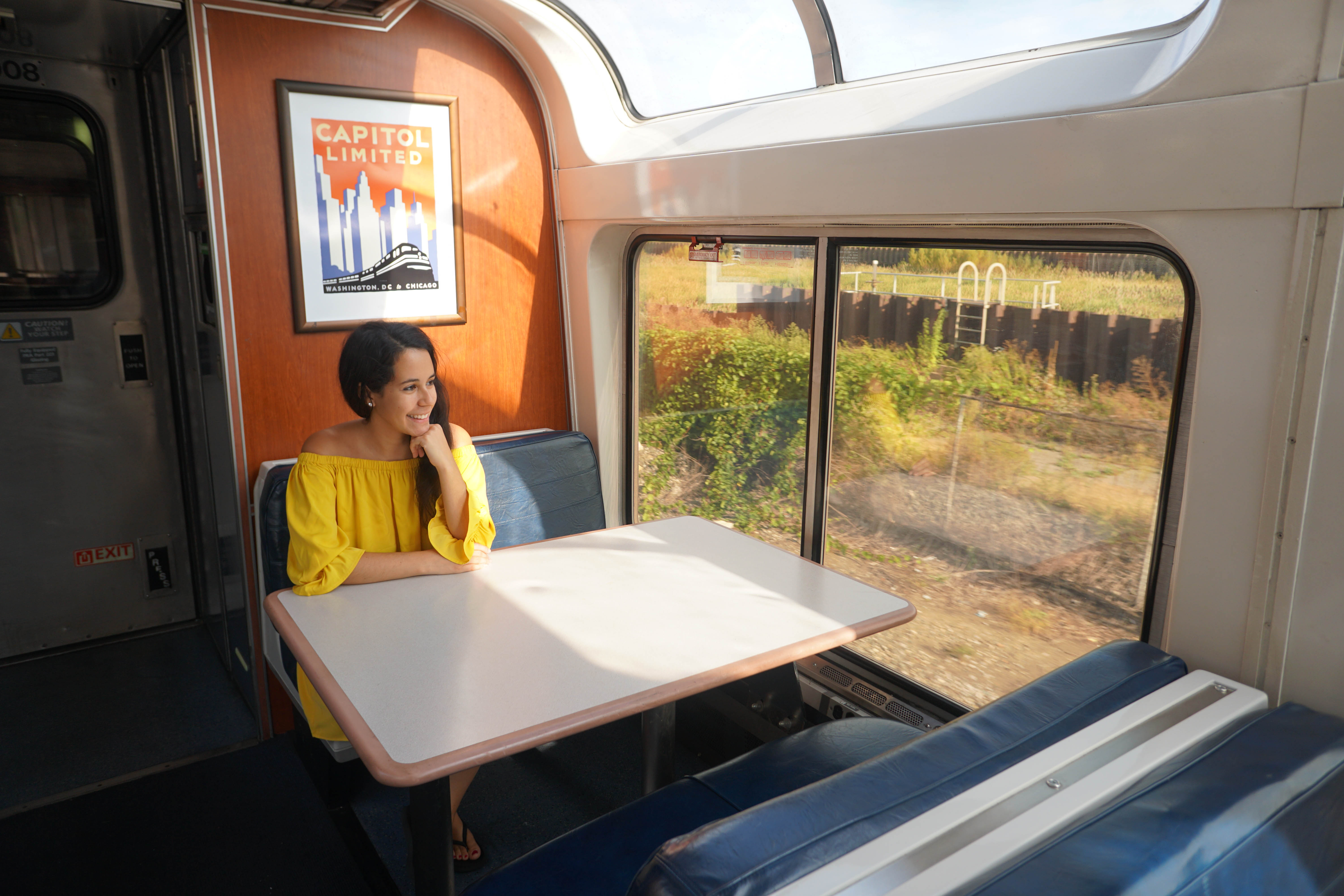 Capitol Limited poster at table with woman looking out window