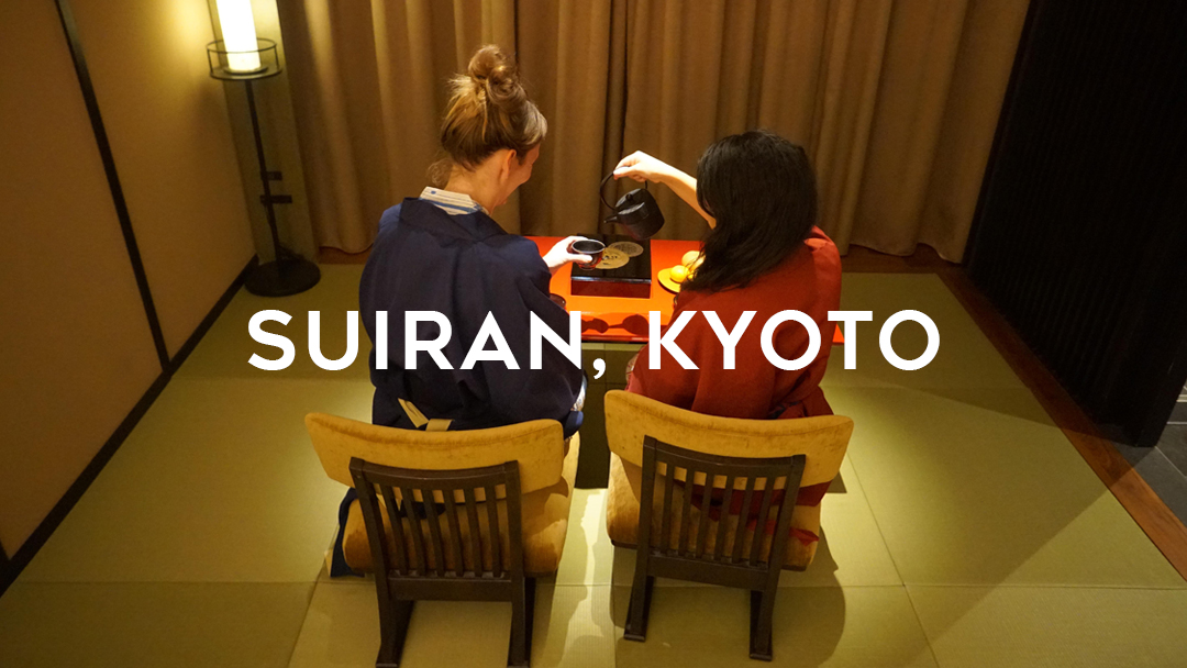 Suiran, Kyoto written over two girls having tea at a red table on the traditional mat and low chairs