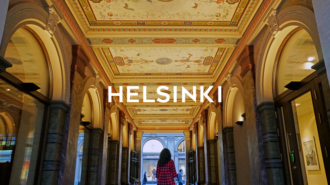 image of passageway with ceiling lights and woman with Helsinki word written on top