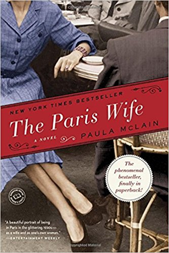 "The cover of ""The Paris Wife book"" with woman below head at a cafe table"