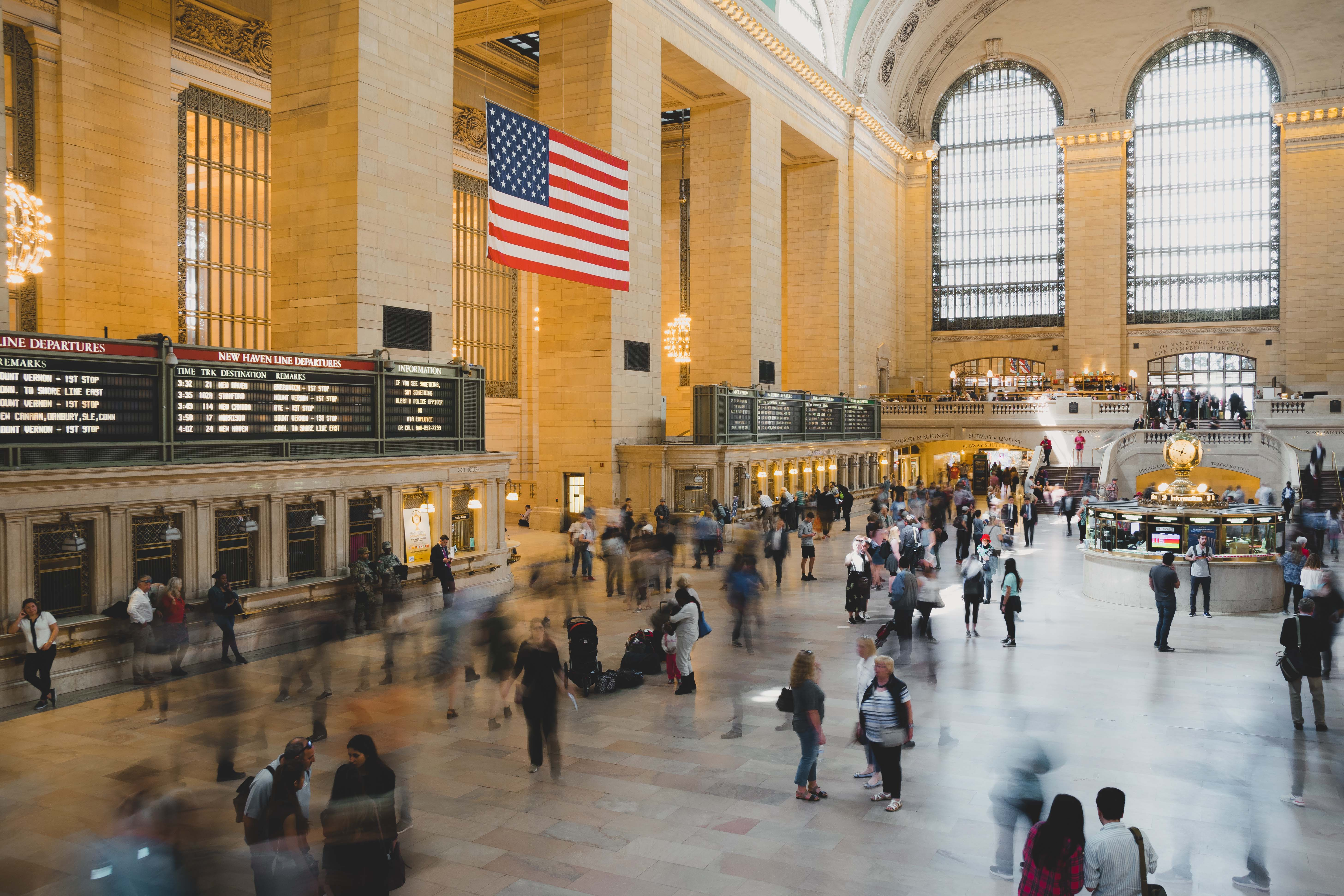 View of main hall in Grand Central long exposure with people moving quickly below the American flag and large windows