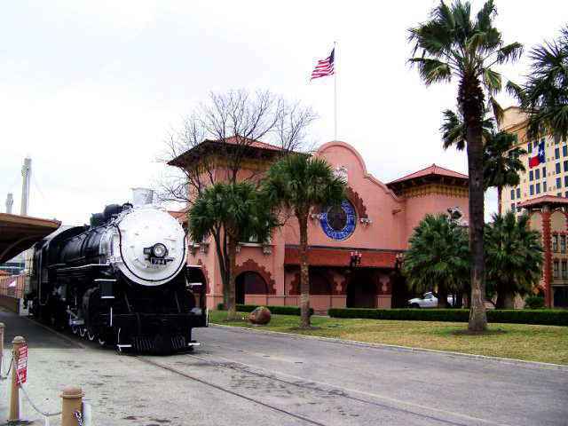 San Antonio's pink train station framed by palm trees and a vintage train
