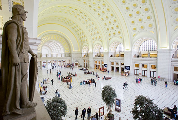 View of a statue overlooking the clean white arched ceilings with gold details in Washington DC's Union Station