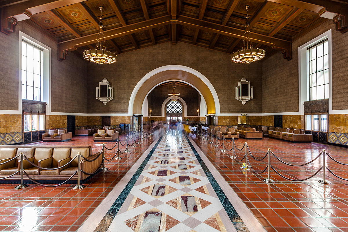 View inside the Los Angeles Train station with the colorful geometric tiles, benches and two chandeliers hanging from the wooden ceiling