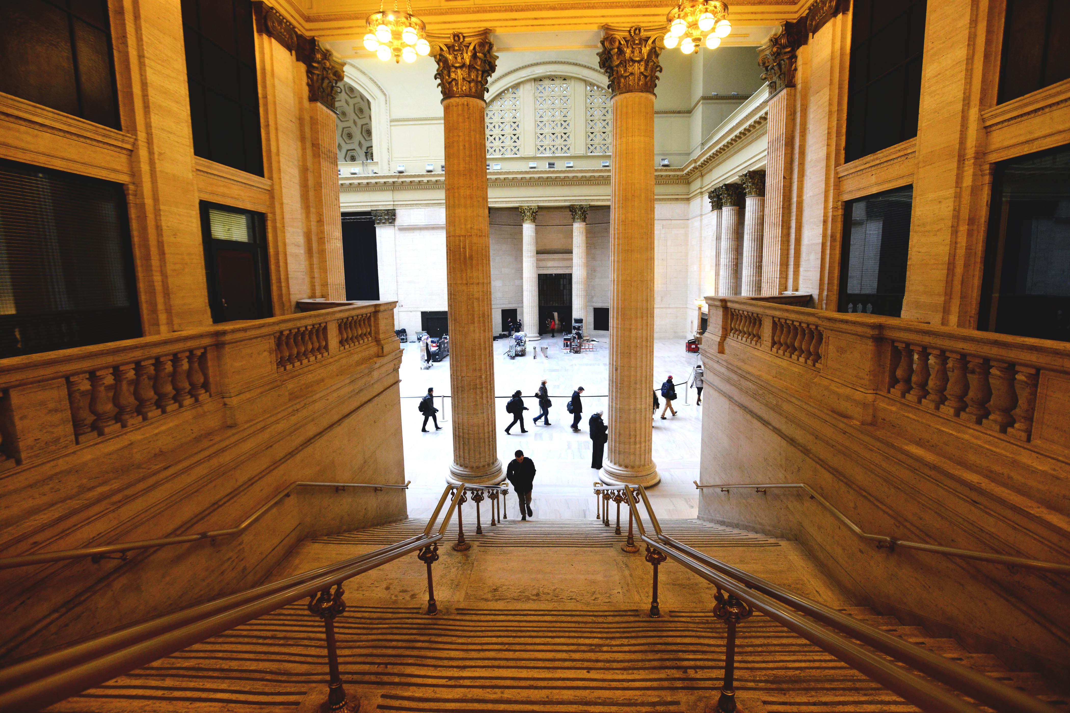 View inside Union Station Chicago of the tall ceilings above a staircase in the main hall with tall columns