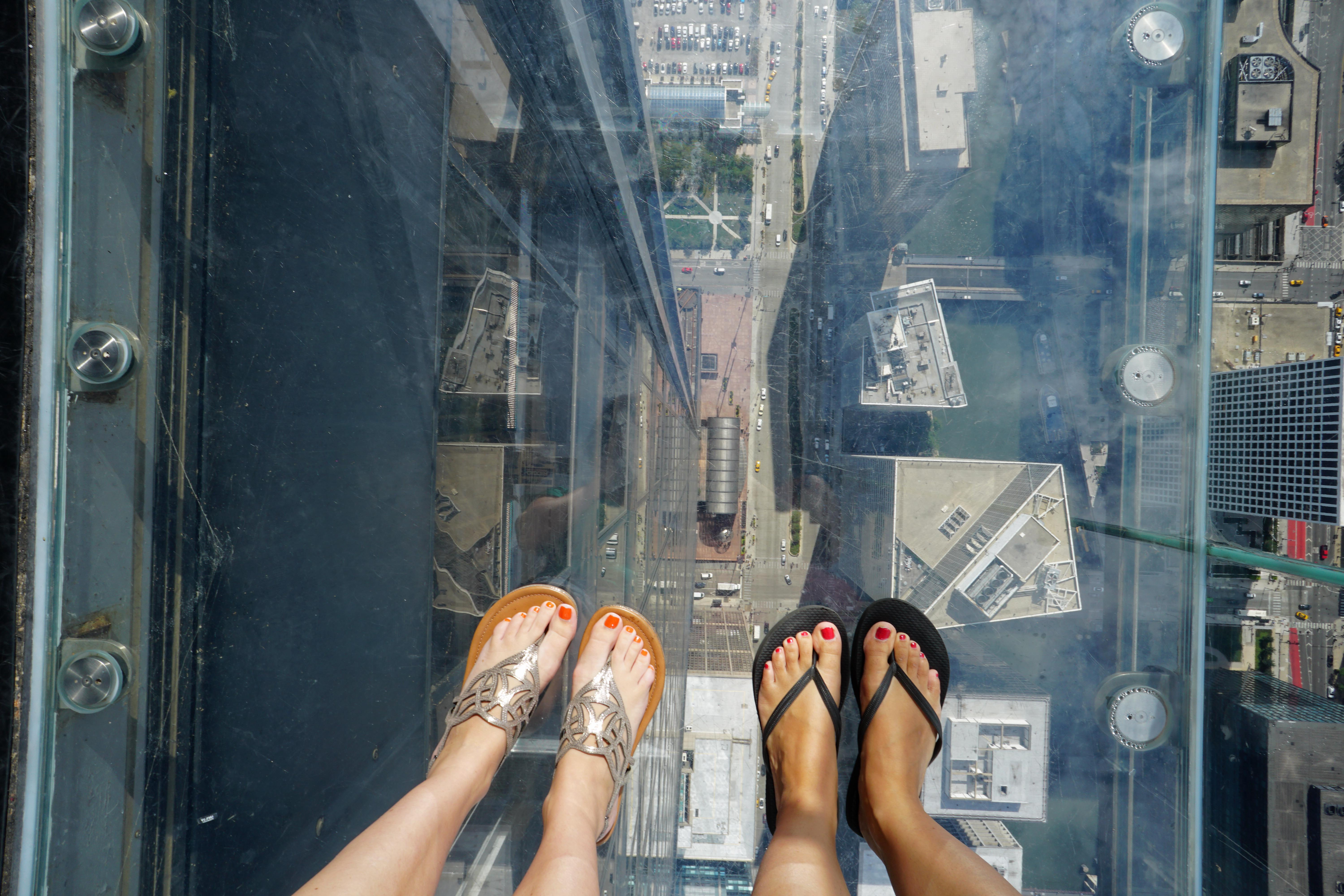 View of our feet looking down through the glass floor of The Ledge