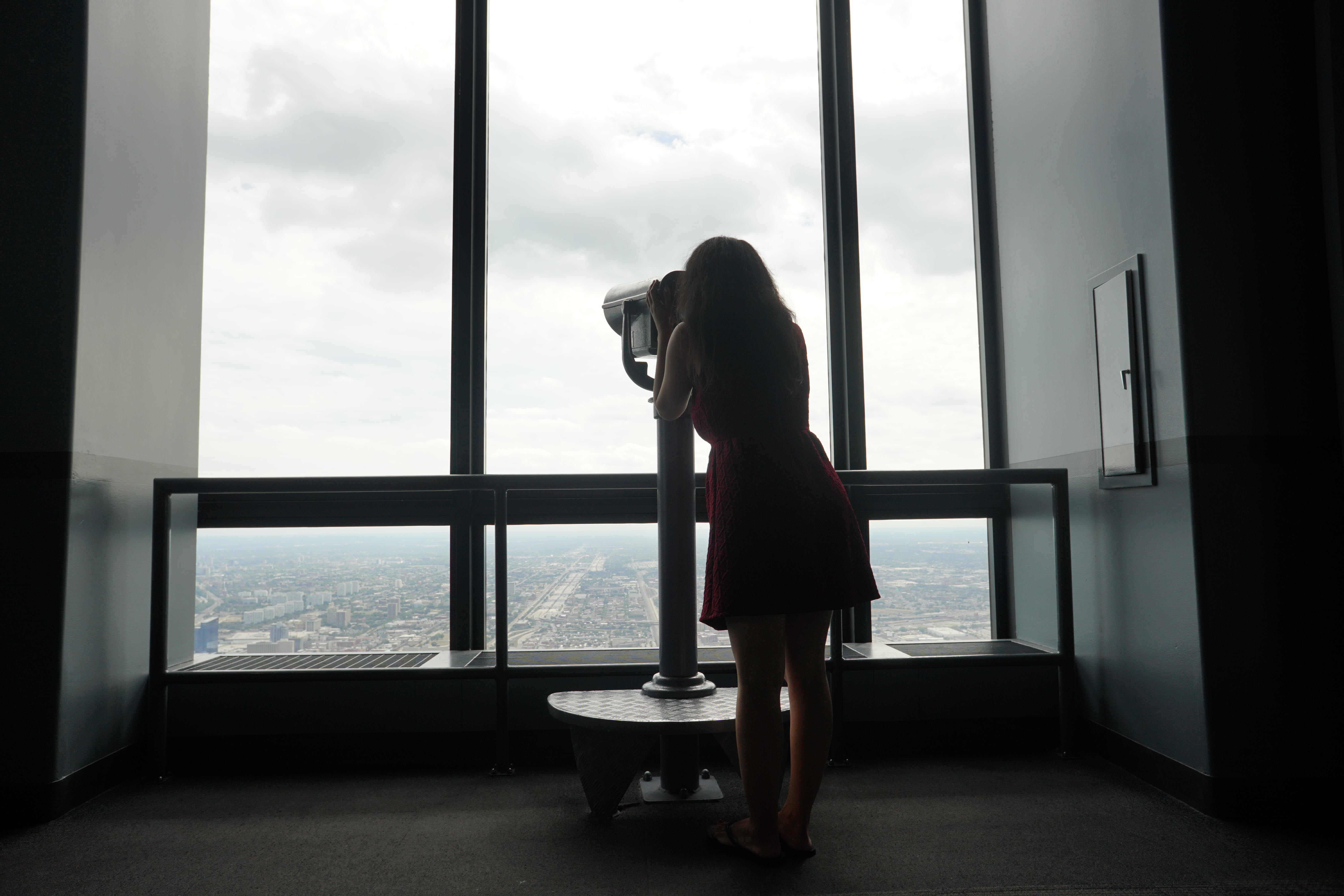 Silhouette of a woman looking through the telescope at Skydeck in Chicago