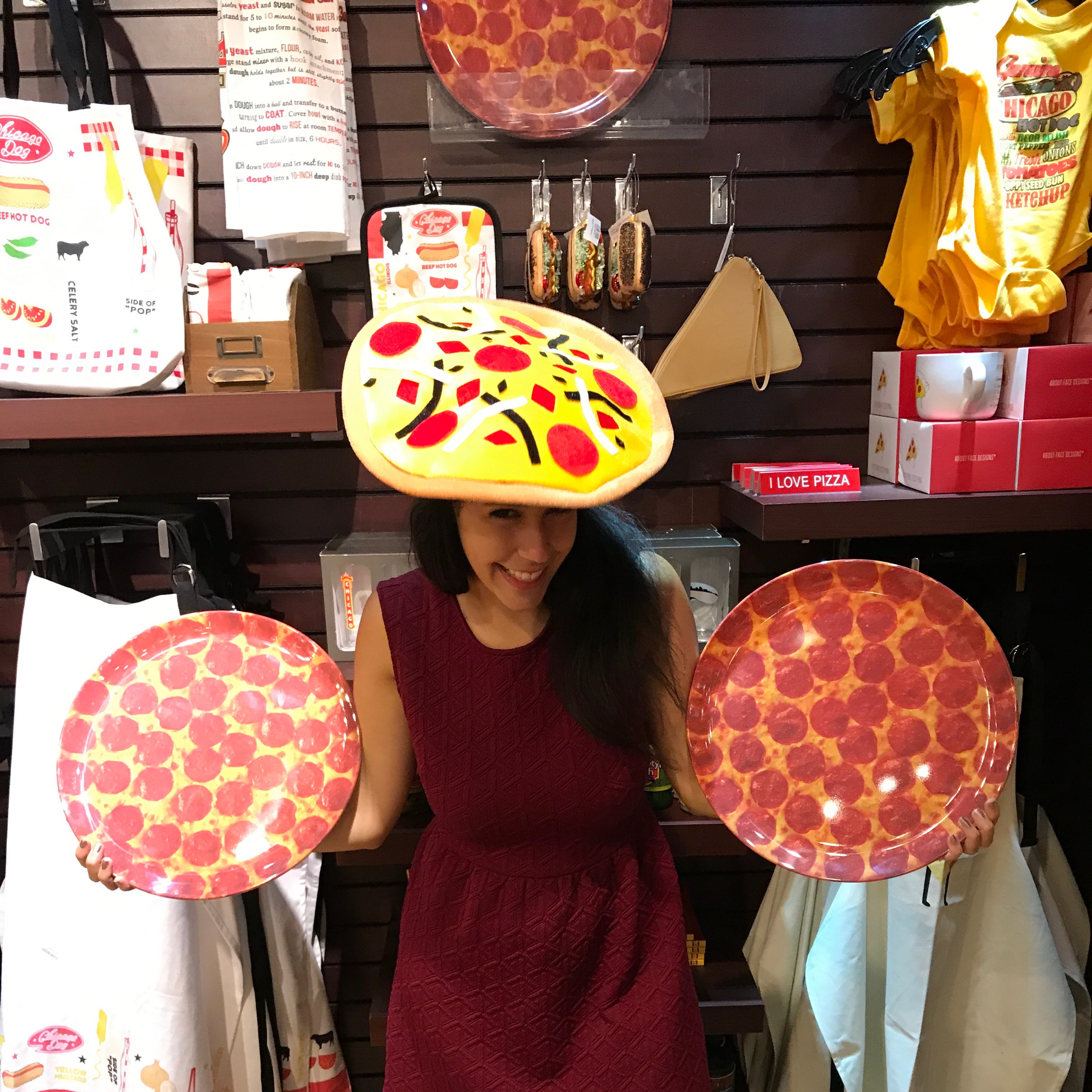 Woman holding up two fake pizzas wearing a pizza hat in front of a background of pizza souvenirs (They probably don't like pizza in Chicago)