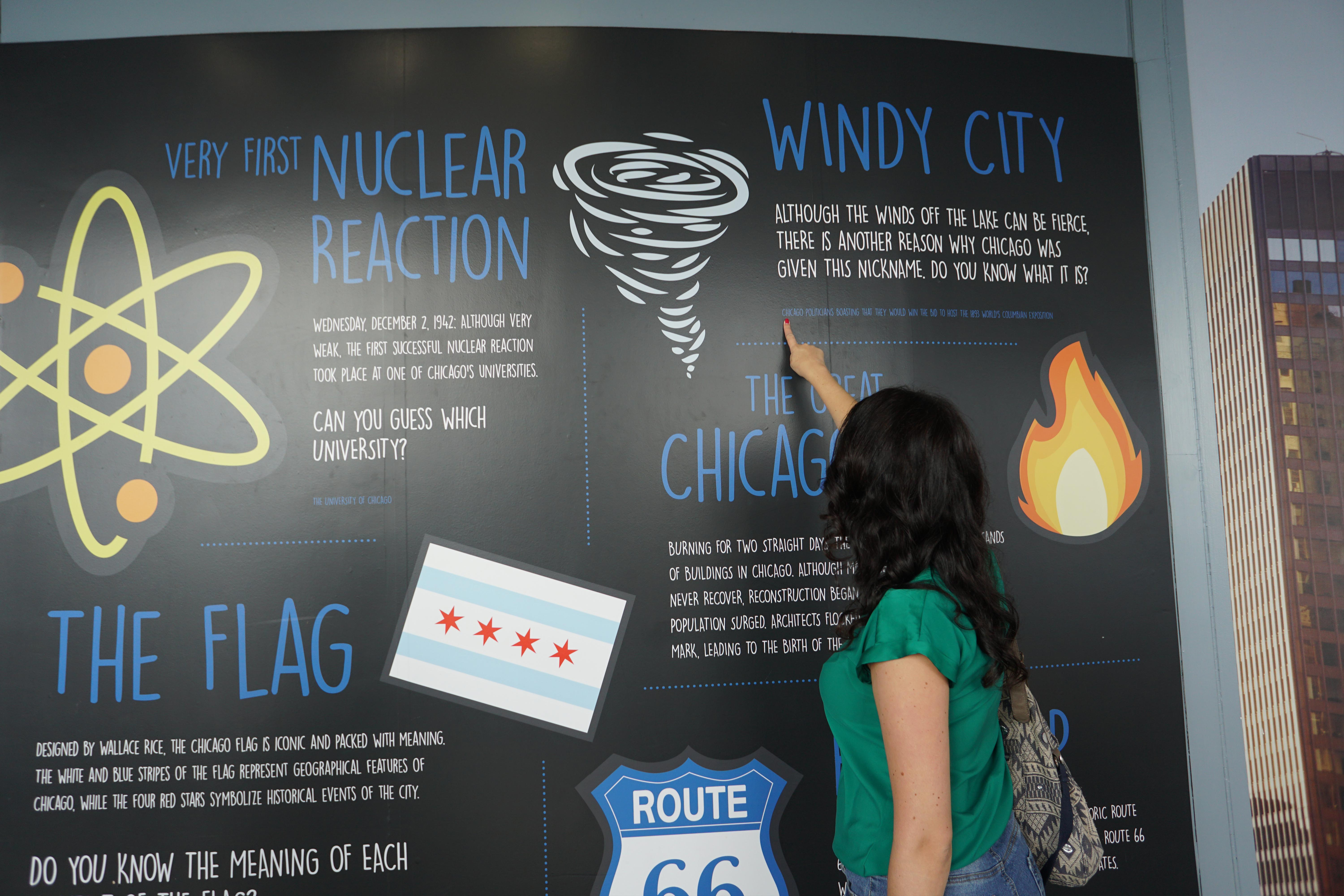"Woman pointing at a fun fact about the ""Windy City"" at The Willis Tower's Skydeck"