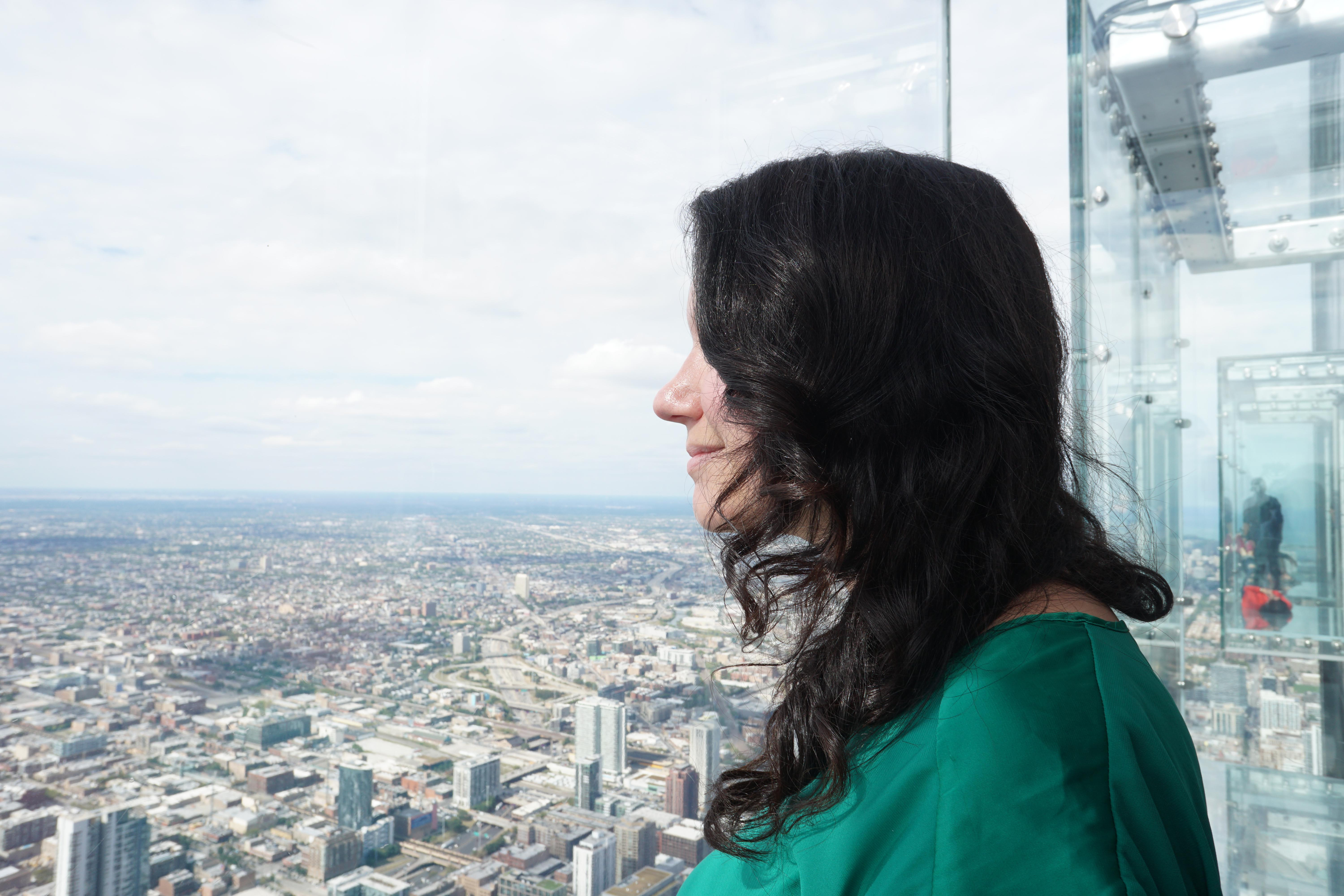 Woman looking out at Skydeck's The Ledge with the other three ledges sticking out of the building behind her