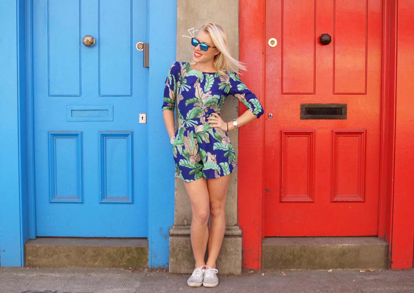 Photo of Louise between a blue and red door wearing a cute thrifted romper with floral pattern