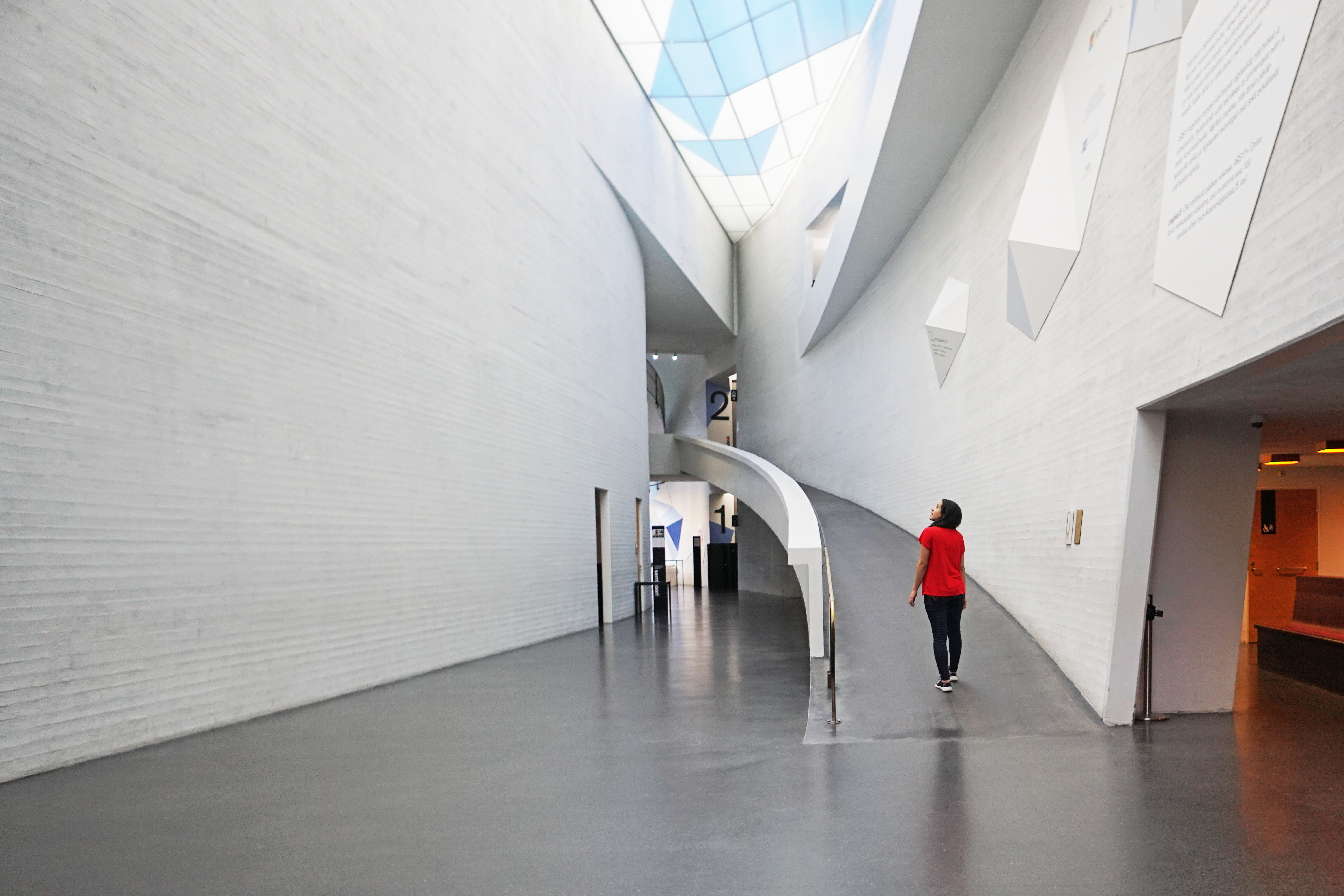 Woman inside large white curved building and curved ramp