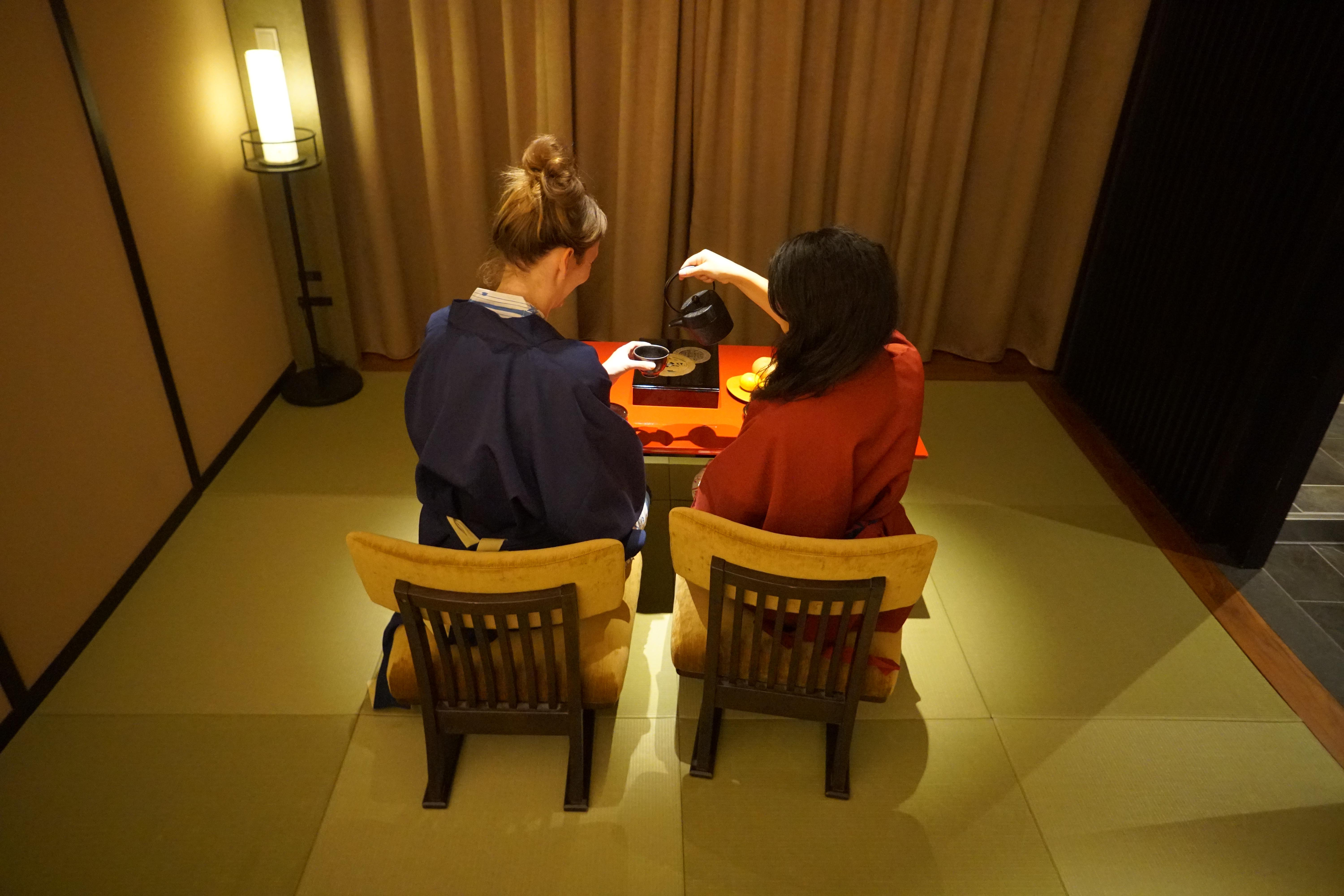 two girls having tea at the table on the matt in the room