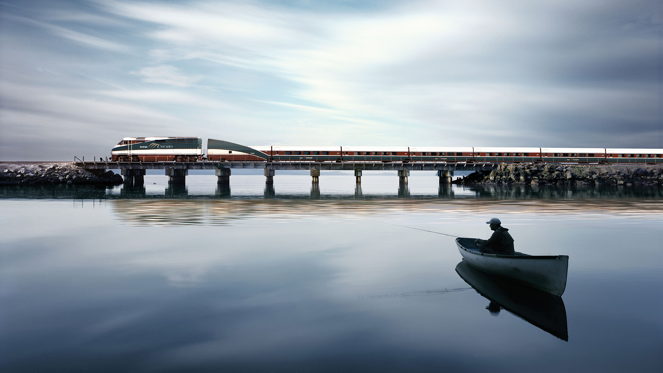 Amtrak Cascades Train Route train over water on a bridge with a man in a boat looking on